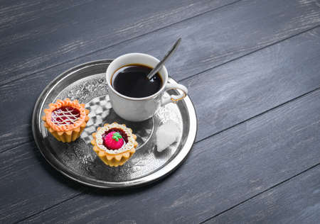 darck: Small cakes petit fours tartlets with jam and cream, metal tray, with white cup of coffee espresso on darck black wooden background, empty clean place for your text