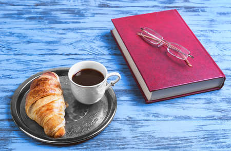 poor eyesight: The small metal round tray breakfast fine white porcelain cup with black coffee and a croissant, book, glasses