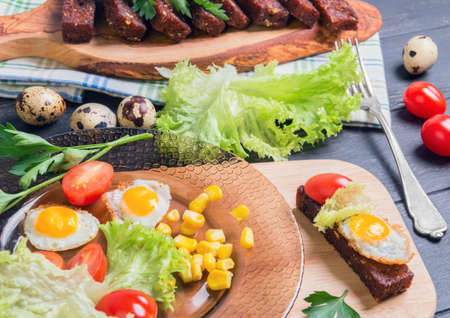 sprigs: Lunch with croutons, tapas, parsley sprigs, quail eggs in shell and fried eggs, lettuce, cherry tomatoes, corn grains on dark wooden background