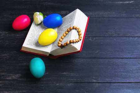 różaniec: Easter card, a small prayer bible, a rosary with a cross, painted eggs red, blue, green, yellow, white rose on a black wooden background
