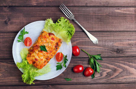 a portion: On a wooden table in a white plate glass portion of the baked cod fish with spices and herbs, cherry tomatoes, lettuce, parsley Stock Photo