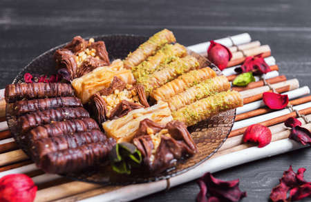 turkish ethnicity: The glass plate and an assortment of baklava and chocolate with nuts, dried flowers red, mat of bamboo on a dark black background in rustic style Stock Photo