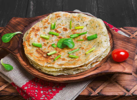 A stack of not sweet frying flour Flatbread Paratha roti, cherry tomatoes, lettuce, napkin of burlap with red lace, wooden board served on a dark black surface