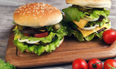 overeat: Two big cheeseburger deluxe high on light wooden background in rustic style