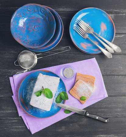 pastila: On a dark background black wooden table in the kitchen cooking biscuit cake pie air apple candy, mint leaves, blue ceramic crockery, top view Stock Photo