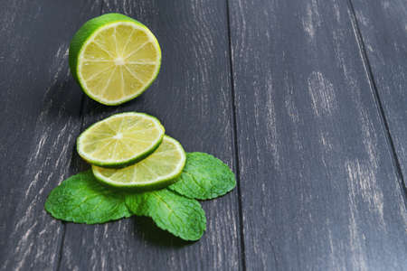 lime slice: Cut into slices of lime and mint leaves on a dark black background wooden table, empty space for your text, recipe Stock Photo