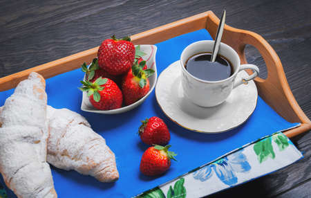 bring: Two croissant sprinkled with powdered sugar, fresh strawberries, hot coffee on a tray for breakfast on a dark wooden background, Empty place for text Stock Photo