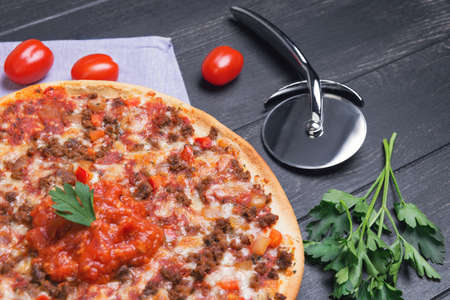 grated mozzarella cheese: Great pizza bolognese on a circular wooden board on a dark black background, cherry tomatoes, parsley, grated mozzarella cheese, sauce