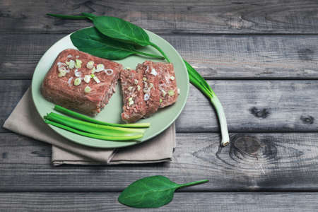 solidify: Jellied meat jelly on a green plate, young onions, spinach leaves on rustic vintage gray wooden background, top view, Empty place for text Stock Photo