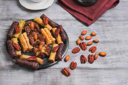baklawa: Baklava walnut, chocolate, almonds, pecans on a round metal tray on a light wooden background