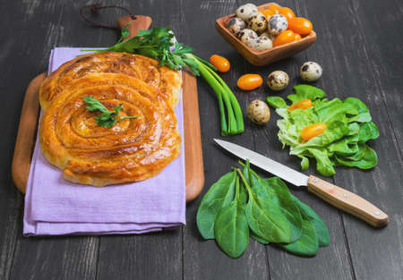 yufka: Pies burek, lettuce, green onions, parsley, yellow cherry tomatoes, quail eggs in a wooden bowl on a napkin on a dark black background in rustic style