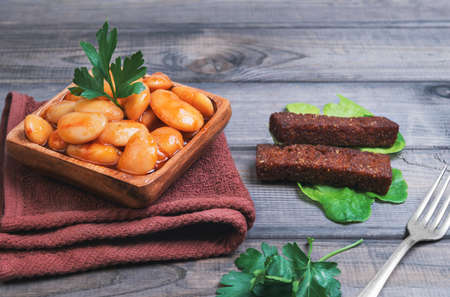 Giant white beans legumes in tomato sauce, parsley, cloth, lettuce, silver fork, croutons on the vintage gray wooden background 版權商用圖片