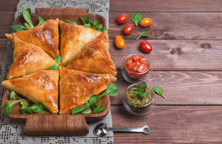 samosa: Delicious deep fried south Indian Samosa pies with meat, lettuce, mint chutney and tomato sauce on a wooden background in rustic style, empty place for text