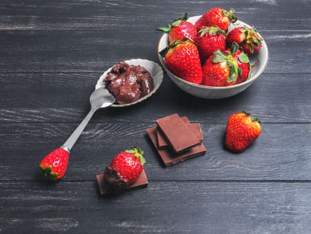 chocolate bars: strawberries in white plate, milk chocolate bars, strawberries in chocolate spread on a black wooden background