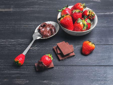 strawberries in white plate, milk chocolate bars, strawberries in chocolate spread on a black wooden background