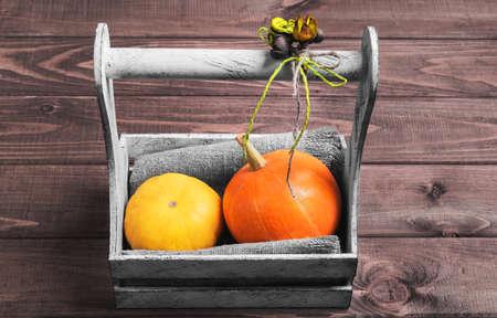 flores secas: Dos peque�as calabazas decorativas de color amarillo y naranja en una caja blanca cesta de madera sobre un fondo de color marr�n, decorado con un ramo de flores secas en estilo r�stico Foto de archivo