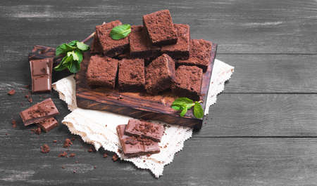 sprigs: Pieces of chopped chocolate cake brownie with nuts, chocolate bars, leaves and sprigs of mint on a cutting board on a black wooden background