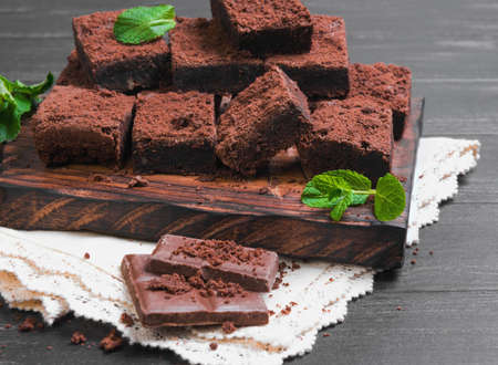 chocolate bars: Pieces of chopped chocolate cake brownie with nuts, chocolate bars, leaves and sprigs of mint on a cutting board on a black wooden background