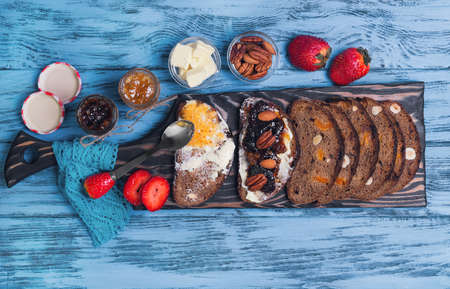 pecans: Sweet dessert sandwiches crostini with lemon jam, plums, pecans, hazelnuts, almonds, strawberries on cutting board on a blue wooden background, empty place for text or recipe, top view