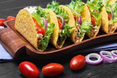 tortilla de maiz: Tacos mexicano de comida, pimientos, tomates cherry, queso rallado, la carne picada en una tortilla de maíz en una bandeja sobre una toalla de lino sobre un fondo de madera negro Foto de archivo