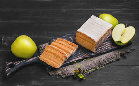 pastila: apple biscuit pie, fresh apples, sacking on a cutting board on a black wooden background surface, empty place for text Stock Photo