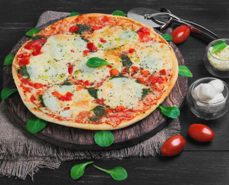 shredded cheese: Big pizza with mozzarella into balls and shredded cheese, cherry tomatoes, lettuce on a cutting board round served on a dark black background wooden surface Stock Photo