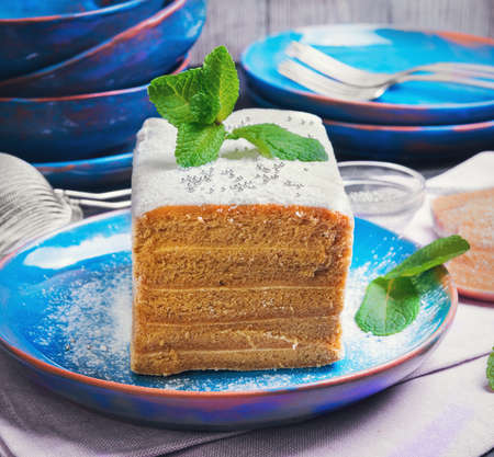 pastila: On a dark background black wooden table in the kitchen cooking biscuit cake pie air apple candy pastila, mint leaves, blue ceramic crockery