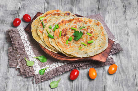 A stack of not sweet frying flour Flatbread Paratha roti, tortillas, cherry tomatoes, lettuce, napkin of burlap with lace, wooden board served on a light white surface