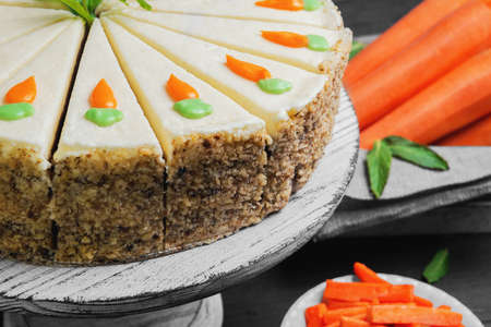 trozo de pastel: Carrot cake pie, sprinkled with nuts, decorated with cream-colored carrots on a stand for cakes, fresh carrots in a white box on a dark black background wooden table in rustic style
