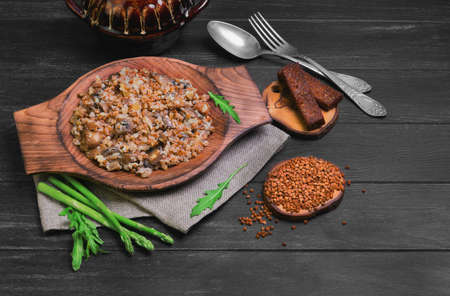 Buckwheat cereal with roasted mushrooms in a wooden plate, raw buckwheat to cereal, asparagus, pot pottery, silver fork and spoon, green lettuce leaves on a dark black background wooden surface Stock Photo