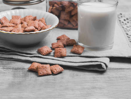 comiendo cereal: Multigrain healthy cereal corn pads chocolate in a white bowl for milk breakfast, glass of milk, cereal bank, cereal is scattered on a table on a light wooden background surface Foto de archivo