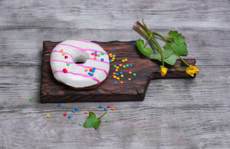 sprinkling: Donut with white and pink icing, sprinkled sprinkling colored for donuts, yellow flowers on a light wooden background