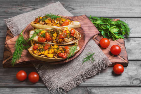 dill and parsley: Vegetarian lunch Baked stuffed white eggplant stuffed with Baked and fresh vegetables, pumpkin, cherry tomatoes, chopped eggplant pulp, dill, parsley on gray background wooden surface, board, burlap