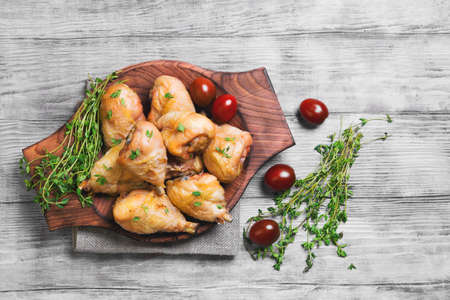 white backing: Chicken poultry meat - legs drumstick chicken with thyme seasoning, fresh thyme on sackcloth, cherry tomatoes on a light shabby white wooden background, top view