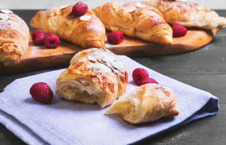 Break in half a croissant, four krussana on a cutting board, raspberries berries, nuts, almonds, powdered sugar on a napkin on black wooden background