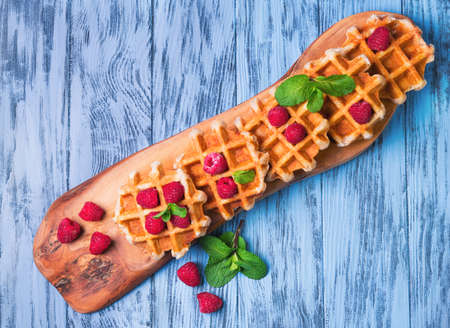 sprigs: Thick lush Belgian waffles, fresh raspberries and sprigs of mint on a cutting board made of wood olive on a blue wooden background surface, top view