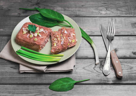 solidify: Jellied meat jelly on a green plate, young onions, spinach leaves on rustic vintage gray wooden background