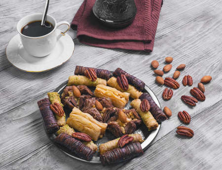 pecans: Baklava walnut, chocolate, almonds, pecans on a round metal tray on a light wooden background