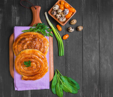 spiral filo pies burek, Greek Bougatsa, lettuce, green onions, parsley, yellow cherry tomatoes, quail eggs in a wooden bowl on a napkin on a dark black background in rustic style, top view, empty place for text, recipe