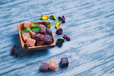 flores secas: Berry marmalade jelly cubes in a wooden square Moscow on blue wooden background surface, a sprig of mint, dried flowers, empty place for text, recipe