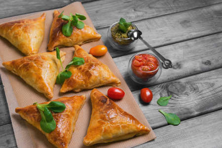 samosa: Delicious deep fried south Indian Samosa pies with meat, lettuce, mint chutney and tomato sauce on a gray wooden background in rustic style, empty place for text, recipe