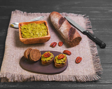 pecans: Italian pesto sauce, rye bagget, small sandwiches bruschetta with sauce pesto, nuts pecans on black wooden background surface Stock Photo