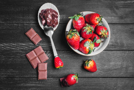 chocolate bars: strawberries in white plate, milk chocolate bars, strawberries in chocolate spread on a black wooden background, top view