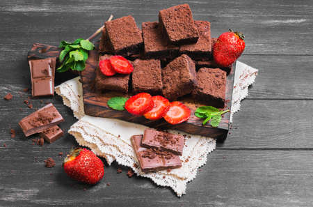 sprigs: Pieces of chopped chocolate cake brownie with nuts, chocolate bars, leaves and sprigs of mint, strawberry berries on a cutting board on a black wooden background Stock Photo