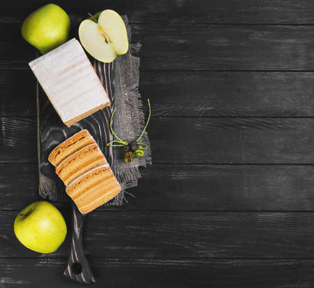 pastila: blank apple biscuit pie, fresh apples, sacking on a cutting board on a black wooden background surface, empty place for text, top view