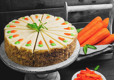Carrot cake pie, sprinkled with nuts, decorated with cream-colored carrots on a stand for cakes, fresh carrots in a white box on a dark black background wooden table in rustic style
