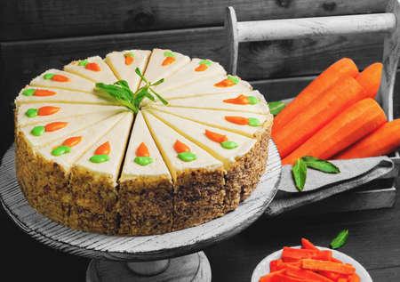 Carrot cake taart, bestrooid met noten, versierd met crèmekleurige wortelen op een tribune voor gebak, verse wortelen in een witte doos op een donkere zwarte achtergrond houten tafel in rustieke stijl