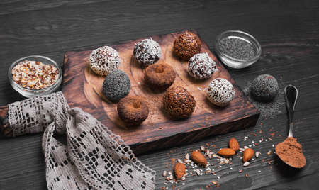 Sweets handmade chocolates sweet-stuff candies, sprinkled poppy, coconut, linseed, sesame, cocoa, almonds oerhi on a cutting board with lace on a light wooden background in rustic style