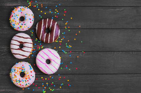 dragees: Multi-colored assortment of donuts with sprinkles and frosting on a dark black wooden background, empty place for text or recipe