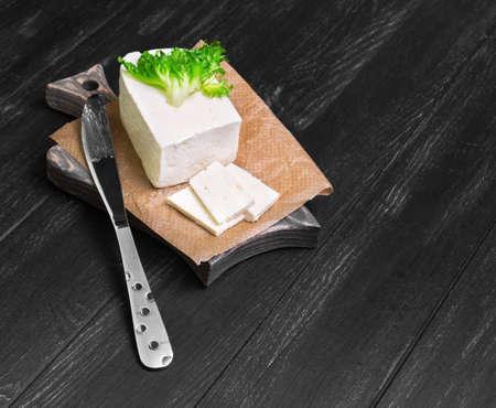 ewes: pickled sheep cheese feta Sirtaki, knife, lettuce on a cutting board on a dark black wooden background